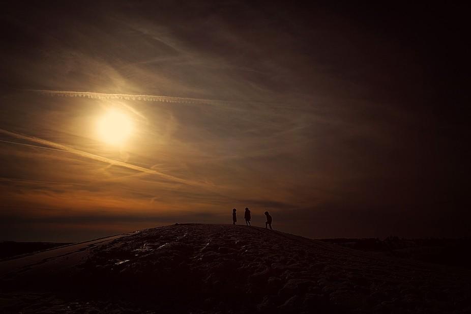 Three children climb a hill in the evening light
