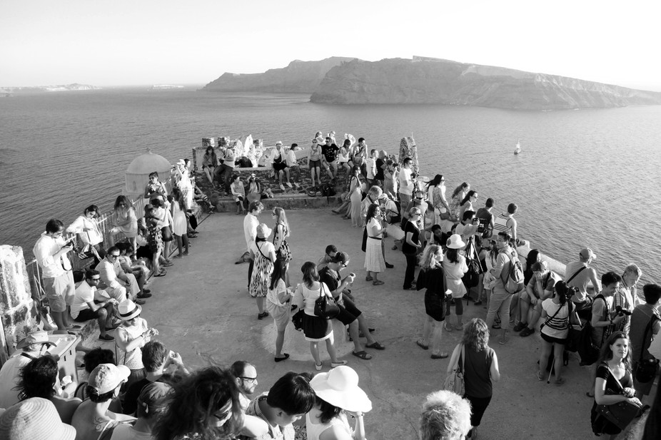 """A large group of tourist in Greece waiting to take pictures of """"The Most Beautiful Sunset in..."""
