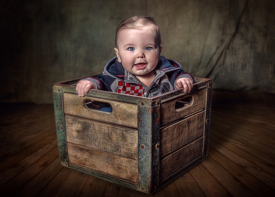 Studio shot of a toddler in an old milk crate.