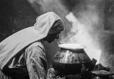 Nun tending kettle fire, Goa, India.