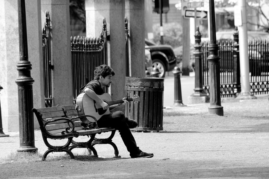 This was a candid street photo of a man playing an acoustic guitar.