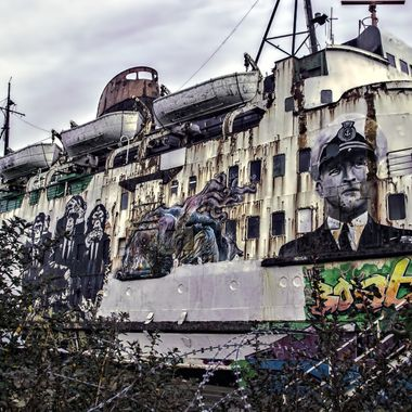 A ship of colour and decay. moored in dry dock for years, painted with graffiti art and unused.