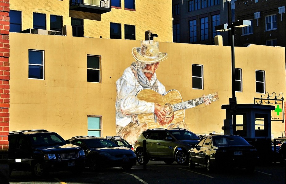 The sun hits an old downtown Denver, Colorado large mural of a cowboy plucking tunes on his old w...