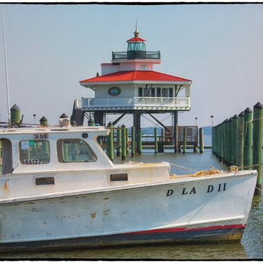 Waterman's boat and the lighthouse that helps them navigate; Choptank lighthouse and with a workhorse of the bay, both waiting for a new season.