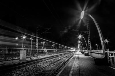 Evening train passing train station.