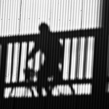 This man's shadow showed up on a wall as he bicycled over me on a bike bridge.