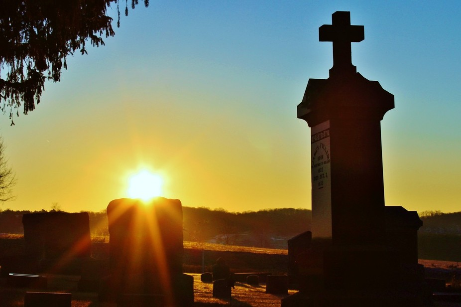 Sun rising, rests peacefully atop a grave stone and it\'s rays are cast brightly on a cross.