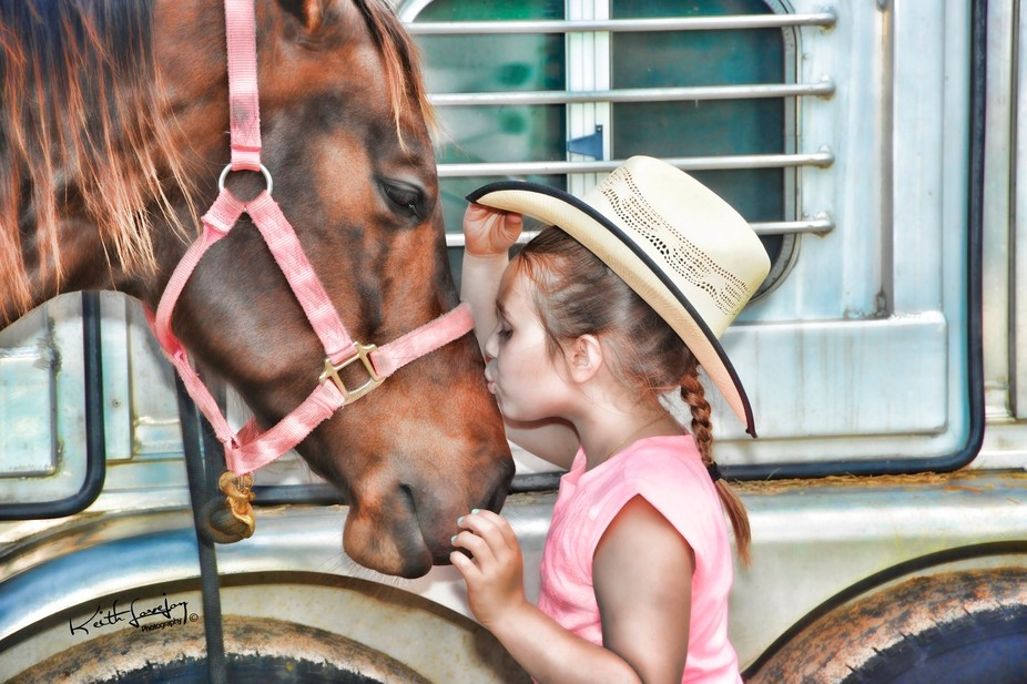 Little girl kissing her horse