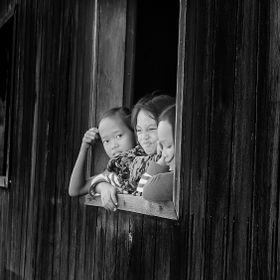 Children were playing in a window on traditional house Central Kalimantan