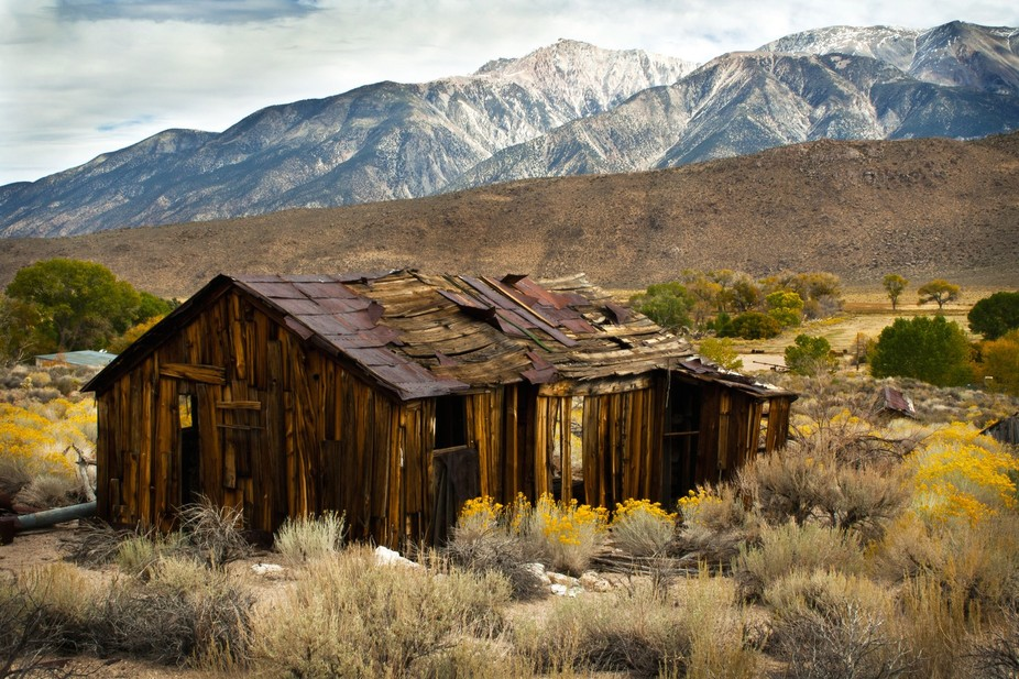 The weathered house just fits.   The rolling hills and snow covered mountains make it shine.  Nos...