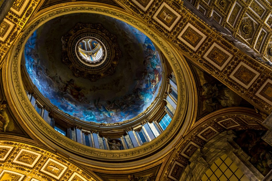 Beautiful ceiling of the basilica in the Vatican, showing lots of blues and golds while looking u...