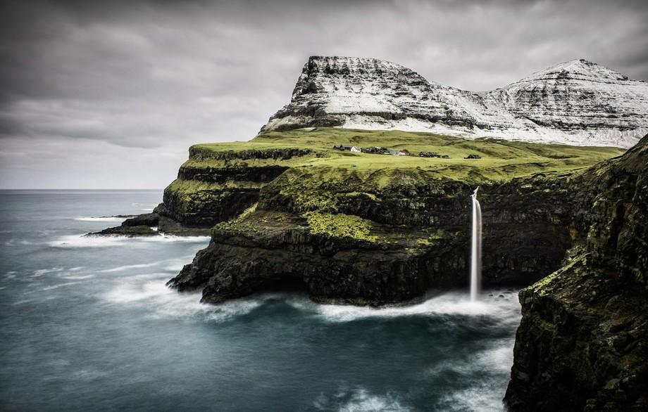 The waterfall at Gasadalur thunders into the heaving North Atlantic surrounding the Faroe Islands...