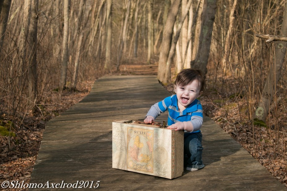 a cute little boy traveling through the woods