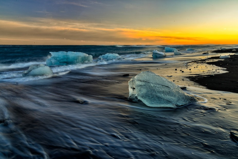 These chunks of ice wash-up on the beach, driven by wind and tides. The ice comes from a nearby g...