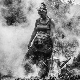 Woman charcoal burning.  Coppice Week 2010  Ashdown Forest, East Sussex. UK