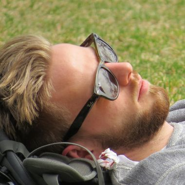A young man wearing Ray Ban glasses takes a nap on the campus of Victoria University in Toronto, Ontario Canada. Close-up.