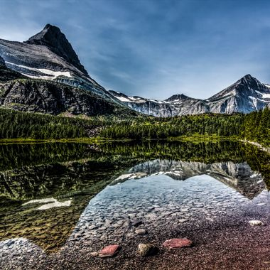 Reflections on a still Redrock Lake in Glacier National Park
