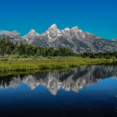 The Tetons reflected in the waters of the Snake River at Schwabacher's Landing in Grand Teton National Park; Jackson Hole, Wyoming