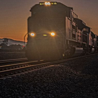 Diesel locomotive racing the sunrise west bound with over 100 freight cars.