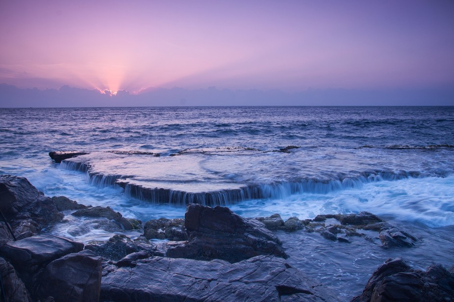 The rock is rising when the tide goes down, letting the water flows over and create a waterfall i...