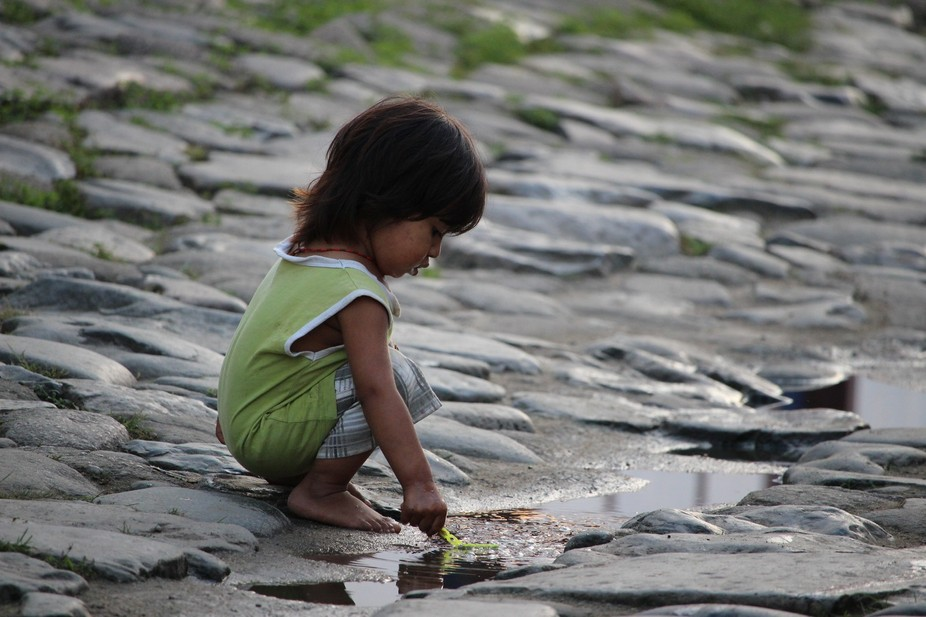 Child from an indigenous tribe playing in water in the streets of Paraty. Rio de Janeiro Brazil