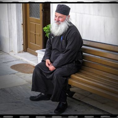 A Greek Orthodox monk with a kind and friendly demeanor, sitting in front of his chapel in the city of Thera, on the island of Santorini