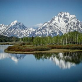 Grand Tetons mountains reflected on the calm, early morning waters of a a lake.