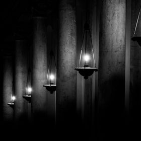 Long dark corridor in black and white, with tall columns illuminated by hanging lamps.
