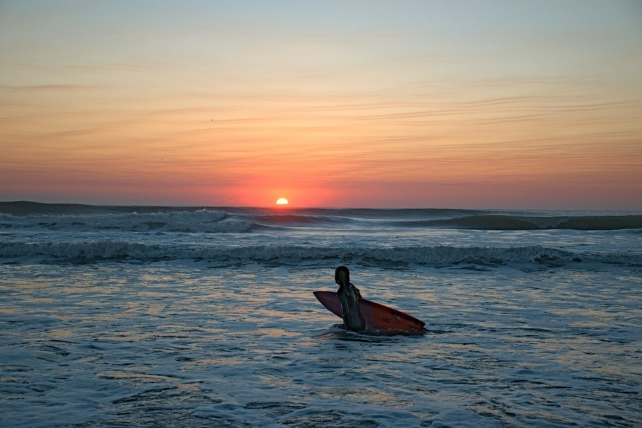 At dawn some guys are enjoying the first waves of the day