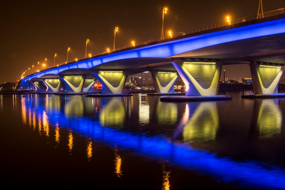 This is a bridge in Dubai with colourful lighting under and at the sides, gives good reflection t...