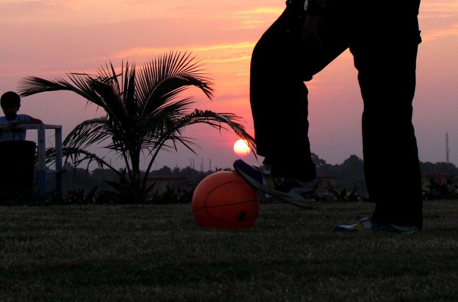 A boy playing of ball but boll is a sun