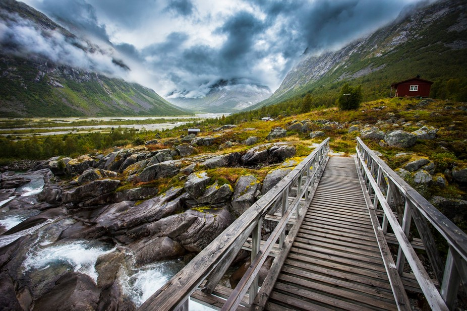 Looking up the glacial valleys of Jostedalen, Norway. The bridge leads us out past the cabins and...