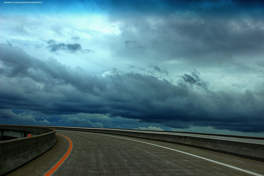 I took this as my wife drove. I just saw the horizon of this highway rise into the storm clouds a...