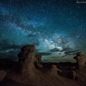 The Milky Way hovers over the spooky hoodoos at Goblin Valley State Park near Hanksville Utah, as storm clouds move through the frame