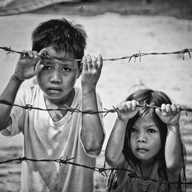 Taken during an outreach activity. They are not imprisoned nor any to that effect, they just happen to be holding the barb wires with their sad f...