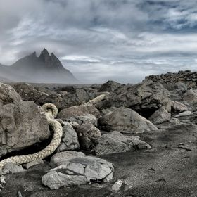 A piece of old rope, washed up on the beach at Stokksnes in Iceland, an old wrecked fishing boat, lies on the rocks in the distance.