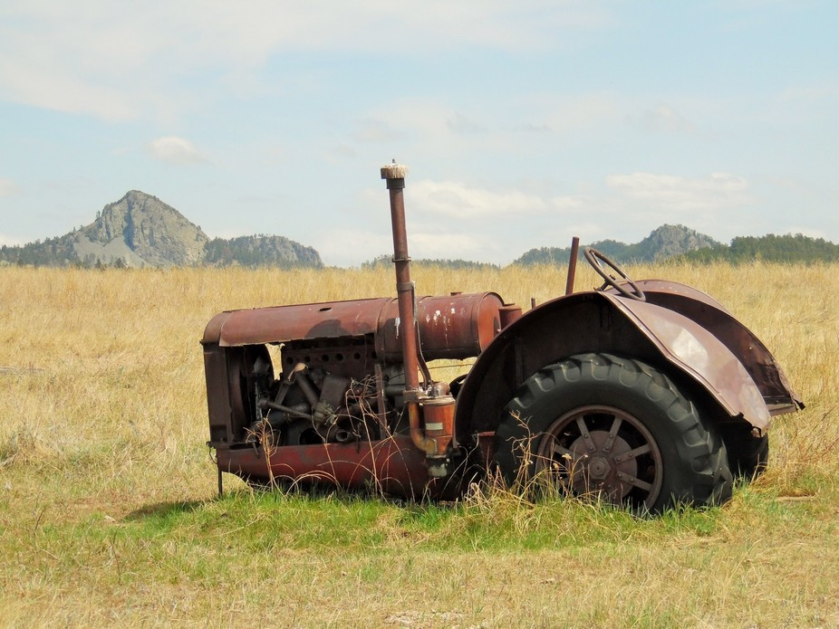 This is an old abandoned tractor with the little Missouri buttes in background.  Located in Wyoming.