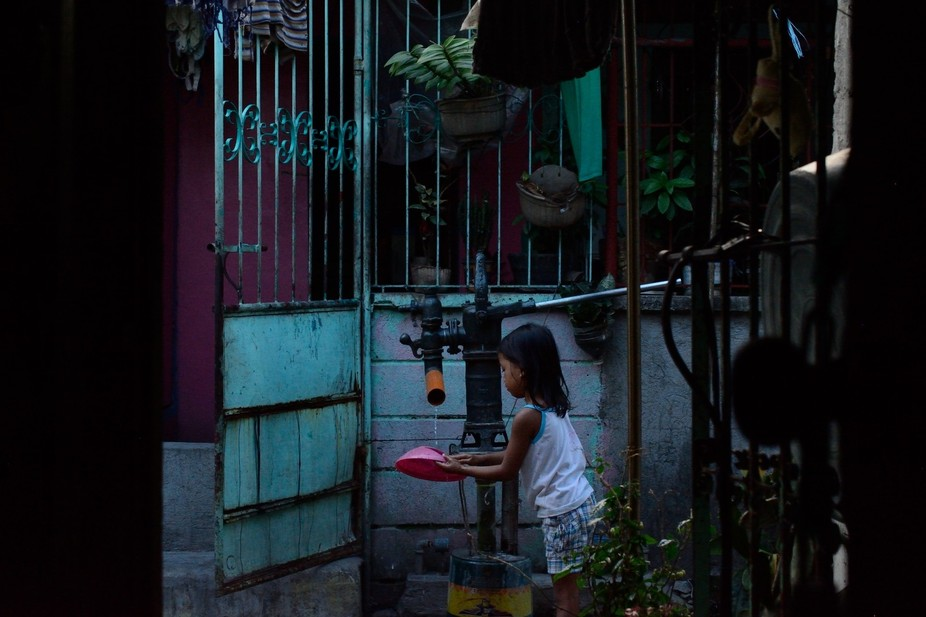 Girl washing a bowl at a well in Santa Rosa City, Philippines. Wells are placed in parts of the c...