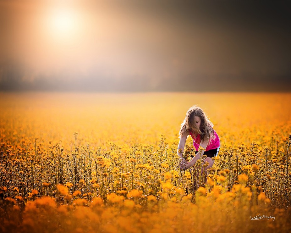 A picture I took of my daughter just before sunset in a field of mustard weed not too far from home.
