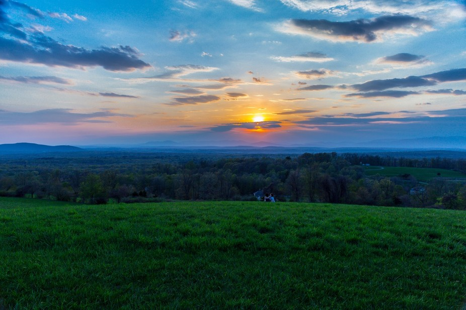 A young couple sit atop Burger Hill in Rhinebeck, NY for another spectacular Hudson Valley sunset.