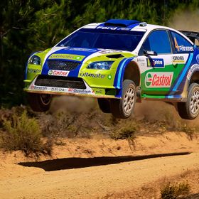 A Ford World Rally Championship competitor on the limit flies his car through the air.