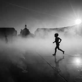 Silhouette of a figure running through the cooling mist of the Miroir d'Eau in Bordeaux, France.