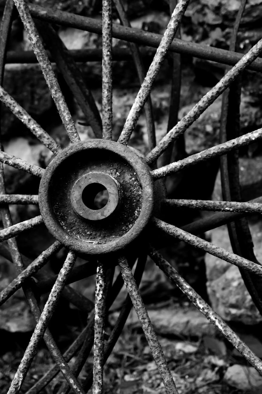 The centre of a rusty old cartwheel with spokes in black and white