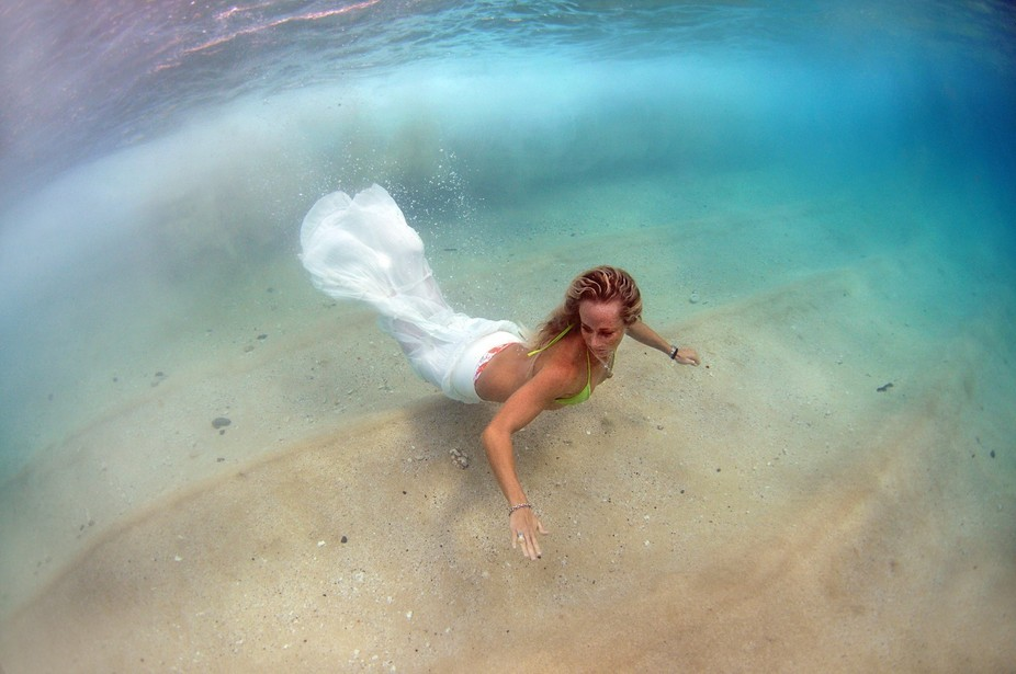 Image of Girl underwater gliding through the surf. Image taken in Hawaii.