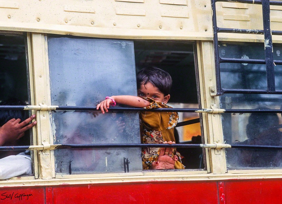 Walking past the bus station in India I came across this little boy staring wistfully out of the ...