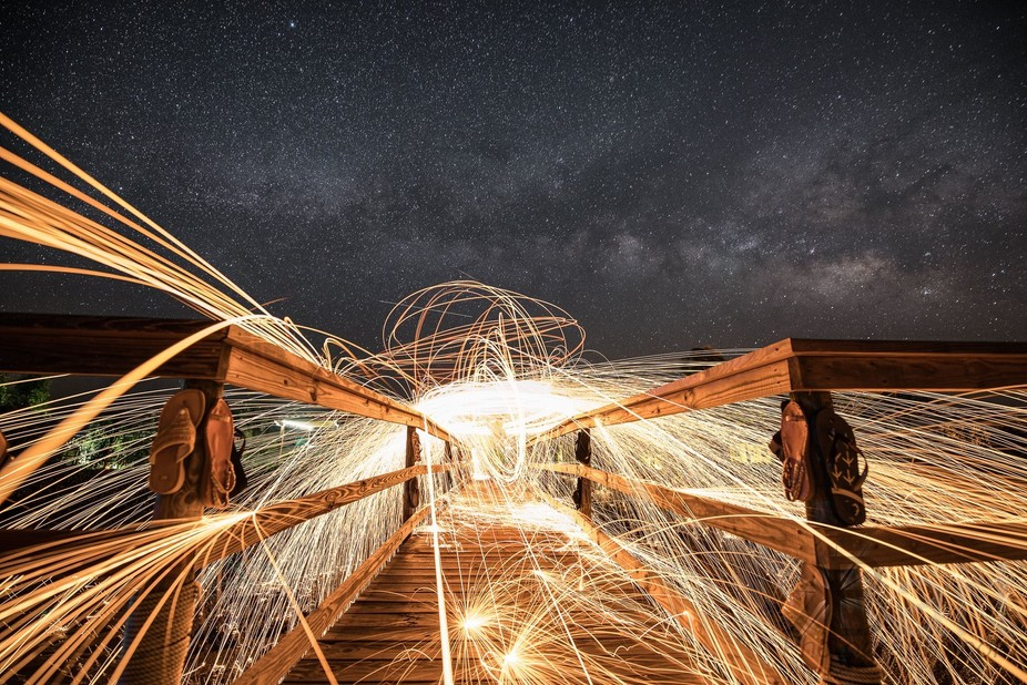 Spark trails under the milky way on the Low Key Hideaway dock. Composite image.