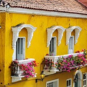 While walking up the ramp to the top of the wall surrounding the old city of Cartagena this beautiful yellow building with balconies covered with...