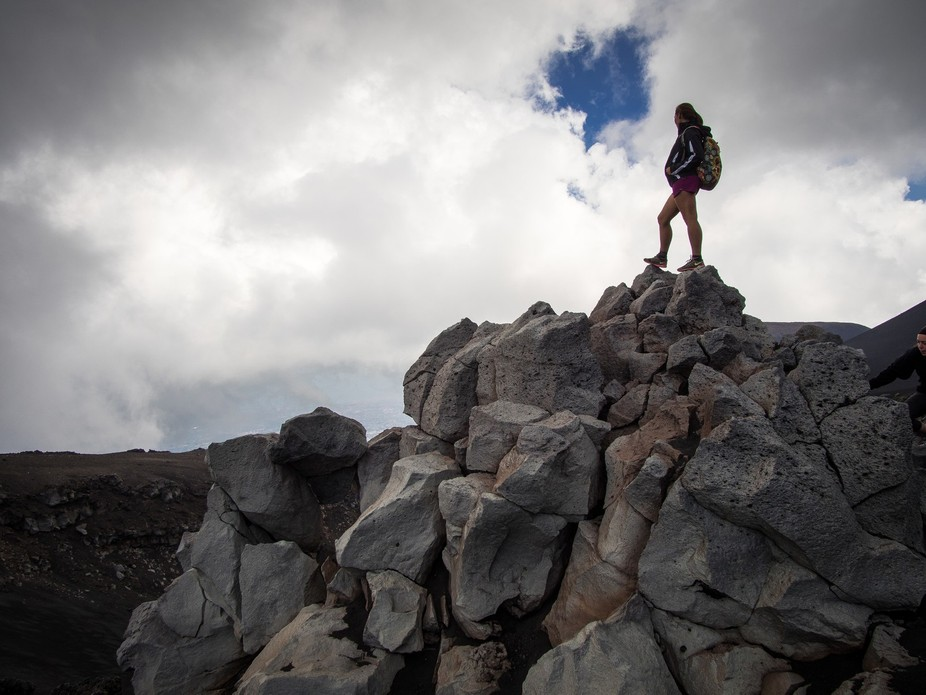 Standing high on a pile of rocks above a volcano crater.