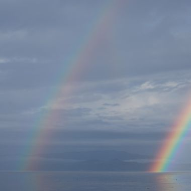 2 rainbows entering the water on Qualicum Beach, B.C. CANADA