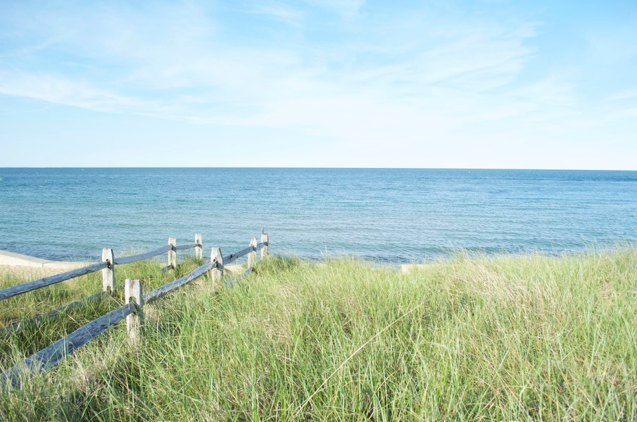 The green grass along a wooden fence that seems to disappear into the blue ocean.